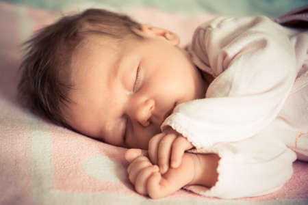natural childbirth: portrait of a newborn baby girl sleeping sideways. She is sleeping on a pink colored blanket Stock Photo