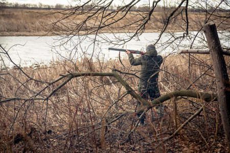 hunter man: Hunter man with gun aiming and prepared to make a shot during hunt