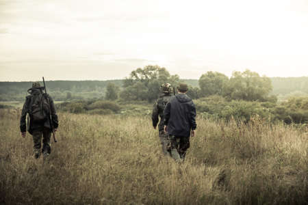 hunters: group of people going up in the early morning in a rural field through the tall grass during hunting season