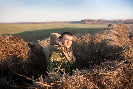 hunter man: Hunter man in camouflage with shotgun camouflage in haystack at rural field at sunrise in early morning