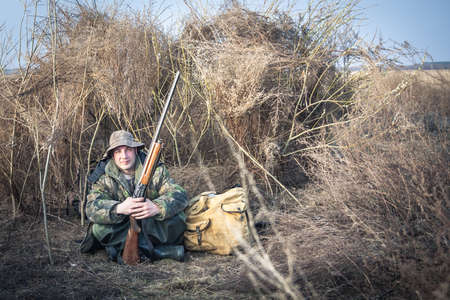 hunter man: Hunter man with shotgun and backpack having a rest in rural field during hunt season Stock Photo
