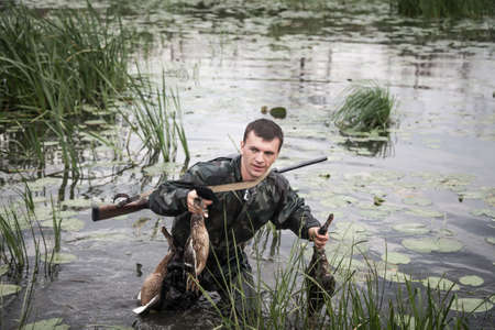 hunter man: hunter man with prey after a successful hunt break through marshland