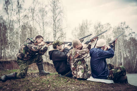 hunters: group of people with guns aimed to the sky and prepared to make a shot Stock Photo