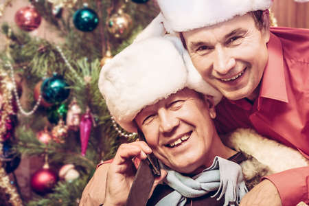 active adult community: Cheerful senior men greeting you with Christmas and New Year holidays by cell phone