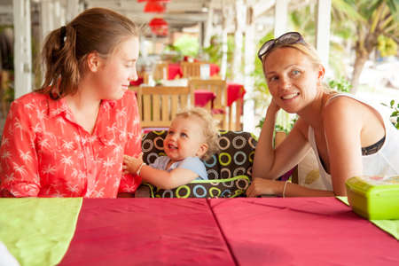Happy young family sitting at table in beach cafe during summer holidays