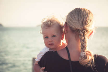 Child with a sincere look hugging his mother sitting on her hands and looking at camera. Mother holding her baby and looking into the distance toward the horizon, child looking at the camera