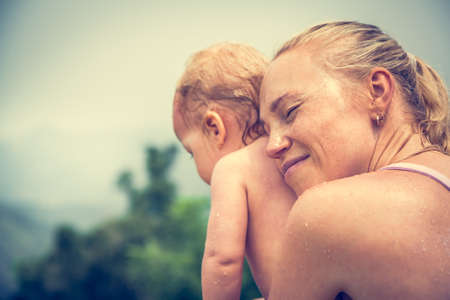 Mother sincerely hugging his child during vacation with copy space. Conceptual picture symbolizing baby care and love Stock Photo
