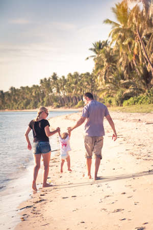 irradiation: Family with child walking together on the beach shore during vacation. Walking together holding each other hands