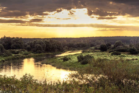 Dramatic sunrise with beautiful rural landscape at river bank with moody sky and sunlight Stock Photo