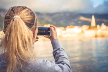 beautiful location: Woman tourist taking mobile photo of beautiful scenery with old town at seashore on mobile phone during travel