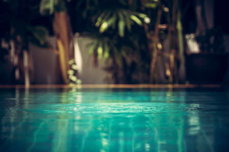 aeration: Swimming pool background in vintage style with ripples on turquoise water and tropical plants on blurred background
