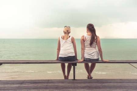 Two young women sitting together and looking into the distance on beach. Concept for togetherness.