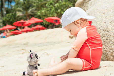 Baby playing with toy on tropical hotel beach. Concept for happy childhood