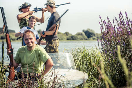 Hunters with guns in boat on river bank during hunting season among reed