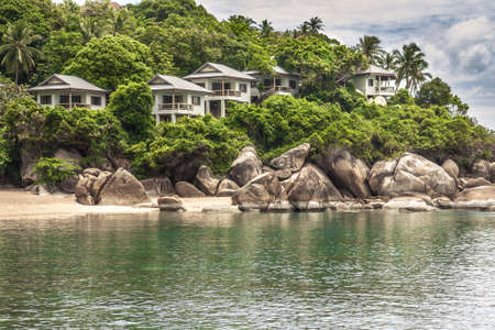 Tropical coast with luxury hotel villas at hillside among lush foliage and palm trees on beach