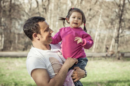 Family portrait of cheerful child and happy smiling dad holding and looking on his daughter.