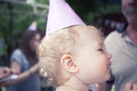 Funny cheerful cute baby girl in birthday cap smiling during birthday party