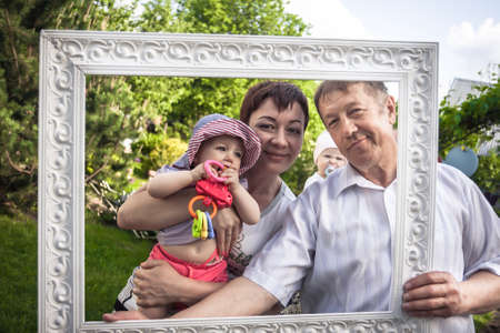 Happy family portrait of cheerful grandfather with his daughter and grandchild during outdoors party