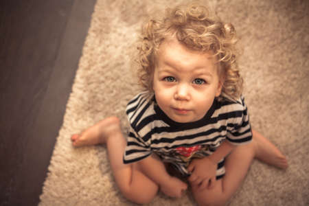 Entreating cute curly baby girl sitting on floor and looking at camera with view from above Stock Photo