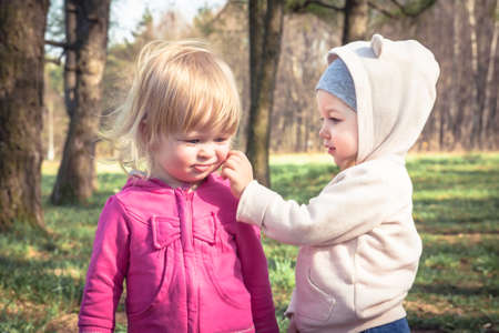 Two cute baby girls playing together in park symbolizing children friendship and childhood
