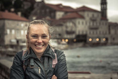 Smiling frozen beautiful woman standing on narrow medieval street  during her travel holidays around Europe in cold overcast rainy day during autumn