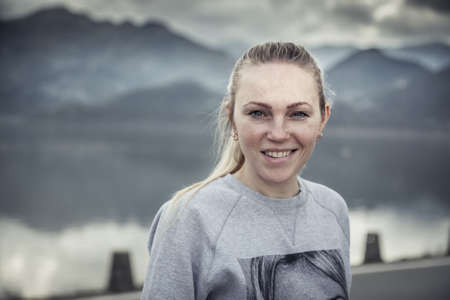 Young blonde smiling woman portrait with with blurred mountains landscape on background in overcast day