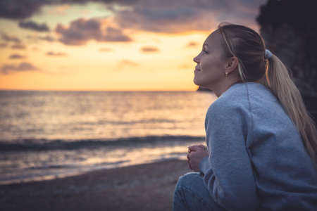 Pensive lonely smiling woman looking with hope into horizon during sunset at beach Imagens