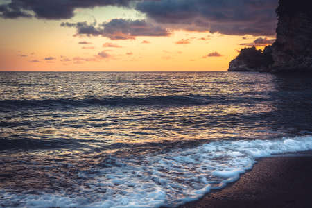 Surf at sunset beach with  vibrant dramatic orange sky and cliffs on Montenegro coastline