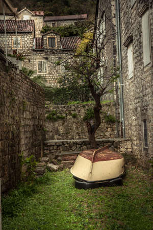 Vintage medieval street with stone building exterior on backyard with overturned old vintage sail boat in overcast day during raining autumn season in old European city Perast with medieval architecture Imagens