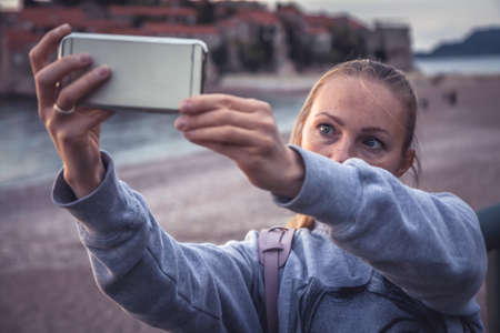 Woman traveler making selfie mobile photo on smart phone during travel holidays at beach for social media networking Imagens
