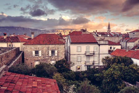 Old European city skyline with orange tile roofs and old building facade in antique architecture with dramatic sky in old European town Budva in Montenegro during sunset Imagens