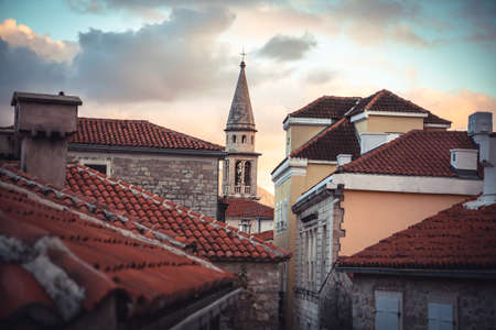 European city skyline with orange tile roofs and tower in front of dramatic sunset sky with antique architecture in old European town Budva in Montenegro Imagens