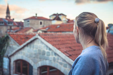 Pensive thoughtful woman tourist looking at beautiful cityscape of old Europe town with orange tile roofs  at sunset during travel vacation