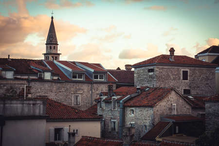 Roofs of Old European city skyline with orange tile and tower in front of dramatic sunset sky with antique architecture in old European town Budva in Montenegro