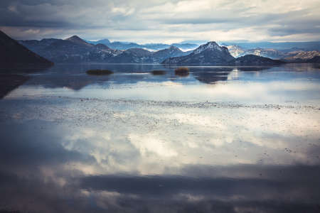 Tranquil water with sky reflection and mountains  landscape in overcast day with dramatic sky in Europe country Montenegro at Skadar lake