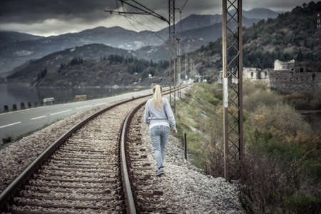 Pensive young woman going away into the distance across railway path in overcast day with dramatic sky  symbolizing parting and despair in relationships