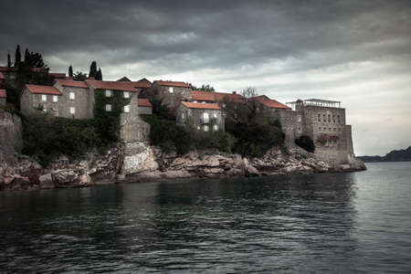 Old ancient buildings on Sveti Stefan island surrounded by sea water on coastline during sunset  with dramatic sky in Europe country Montenegro in fall season