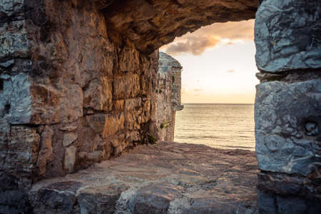old ruins background with scenic sunset over sea through ancient castle window with dramatic sky and perspective view with effect of light at the end of tunnel as travel background