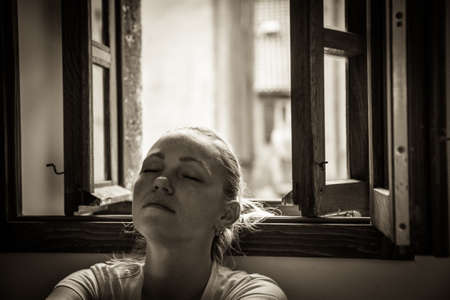 pensive young woman with closed eyes lost in thoughts relaxing and dreaming near opened  window in black and white color in vintage style with dramatic mood