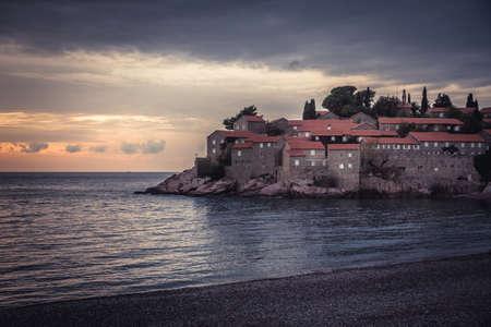 Old town Sveti Stefan on coastline  during sunset  in European country Montenegro Imagens