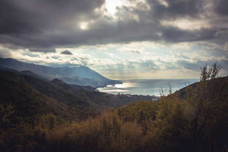 Mountains landscape on sea coast  with dramatic sky and sun rays during sunset in Europe country Montenegro Imagens