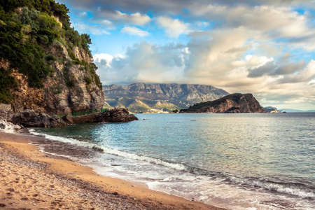 Scenic beach with cliff and rocks surrounded with vibrant transparent turquoise water during sunset in Europe country on Montenegro coastline on Balkan peninsula