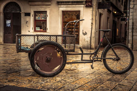 Retro bicycle on vintage europe medieval plaza with stone pavers in overcast day during raining autumn season in old European city Kotor with medieval architecture