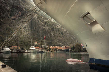 Marine sea port with moored cruise nautical vessel in medieval Kotor bay in Montenegro in overcast rainy autumn day