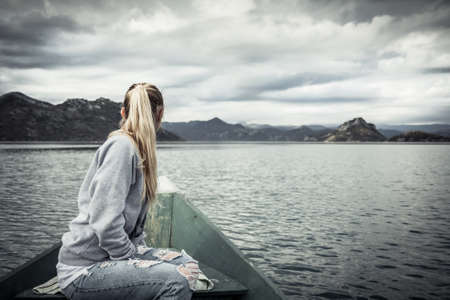 Pensive young woman tourist looking at gloomy landscape on bow of boat floating on water  towards shore in overcast day with dramatic sky