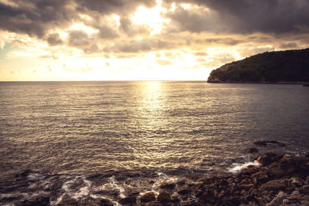 Sunset pebbles beach with dramatic golden sky and water surface on coastline Imagens