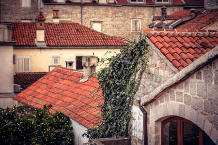 Ancient building facade in old European city with orange tile roofs with antique exterior in retro vintage style