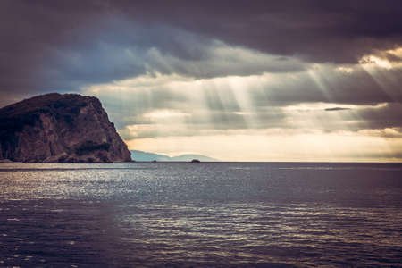 Scenic landscape with cliff rock at sea during sunset with sun rays breaking through dramatic clouds  during sunset and copy space