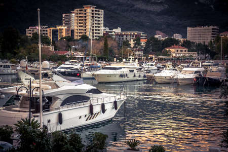 Luxury yachts and boats moored  in sea port during sunset