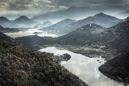 Mountains landscape with river creek around Rijeka Crnojevica river from high view in overcast day with dramatic sky in Europe country Montenegro Imagens
